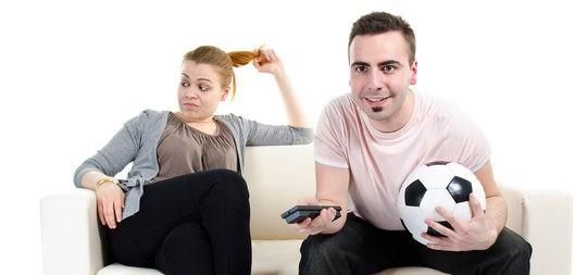Chica aburrida mientras su novio ve un partido de fútbol