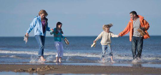 Una familia paseando por la playa